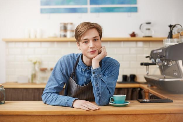 Bel barista maschio che indossa camicia di jeans e grembiule a righe grigie.