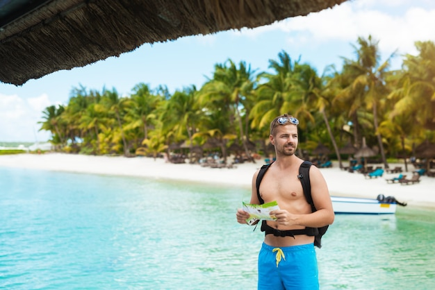 Симпатичный мужчина в пляжной одежде на удивительном тропическом фоне
