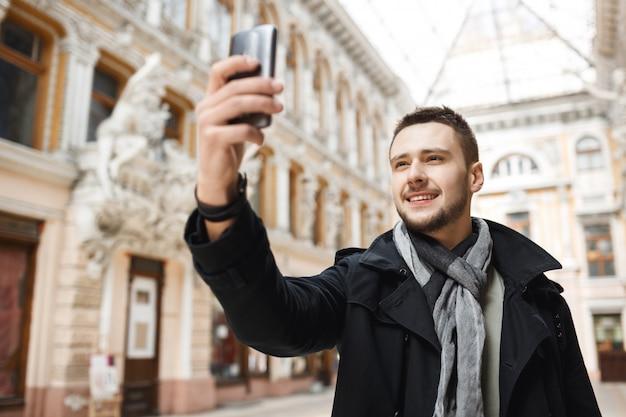 Хороший человек принимая selfie во время прогулки по красивому городу.