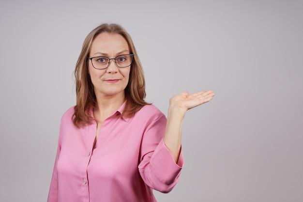 眼鏡をかけたピンクのブラウスで素敵な成熟した実業家