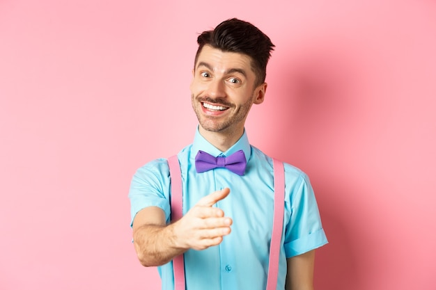 Nice to meet you. handsome young man stretch out hand for handshake, smiling friendly and polite, introduce himself, standing over pink background.