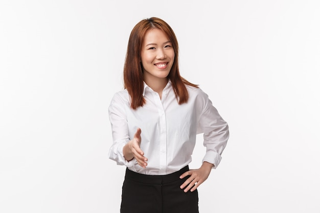 Nice to meet you. polite and friendly smiling successful businesswoman greeting client or business partner, extend hand for handshake as saying hi, pleased to know you, white wall