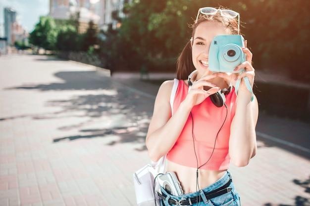 素敵なメロディックな女の子がカメラのレンツを探しています。彼女は微笑んでいる。女の子の首にはヘッドフォンがあり、音楽プレーヤーは体の近くにあります。彼女は幸せだ。