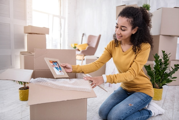 Nice memory. joyful curly-haired girl packing a framed photo into a big box and smiling widely while preparing for moving out