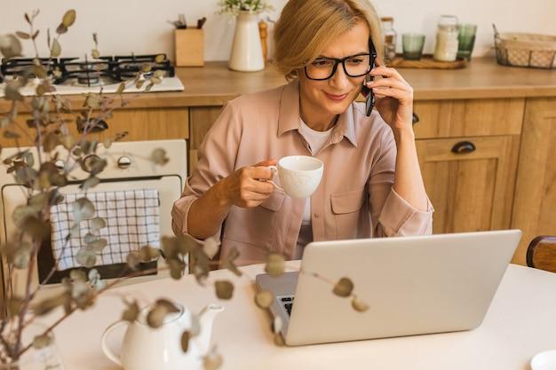 おはようございます。キッチンに立って、朝食後に休んでいる間彼女のラップトップを使用して、家で働いているフリーランサー、陽気な笑顔の年配の女性。携帯電話を使う。