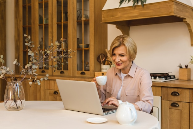 おはようございます。キッチンに立って、朝食後に休んでいる間彼女のラップトップを使用して、家で働いているフリーランサー、陽気な笑顔の年配の女性。
