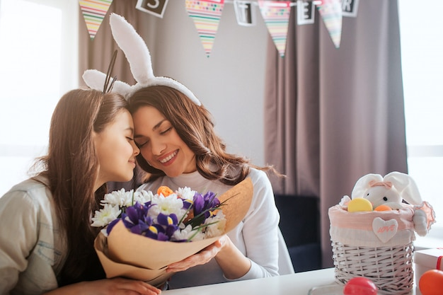 Nice mother and daughter prepare together for easter in room. they sit and hug each other. young woman hold beautiful bouquet of flowers. calm and happy.