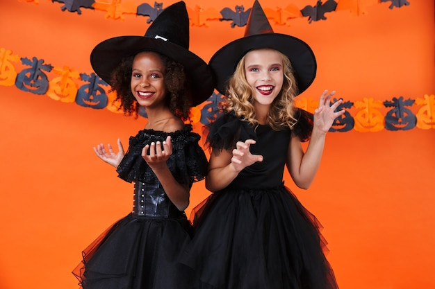 Nice multinational girls in black halloween costumes smiling and making fun isolated over orange pumpkin wall