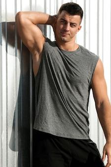 Bel uomo muscoloso. ritratto di uomo bello atleta fitness in posa all'aperto