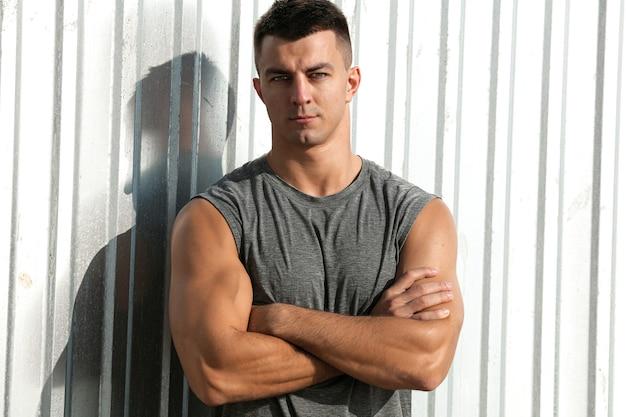 素敵な筋肉質の男。腕を組んで屋外でポーズをとるフィットネスアスリートハンサムな男の肖像画