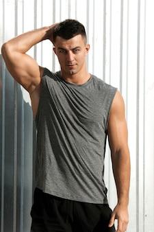 素敵な筋肉質の男。屋外でポーズをとるフィットネスアスリートハンサムな男の肖像画