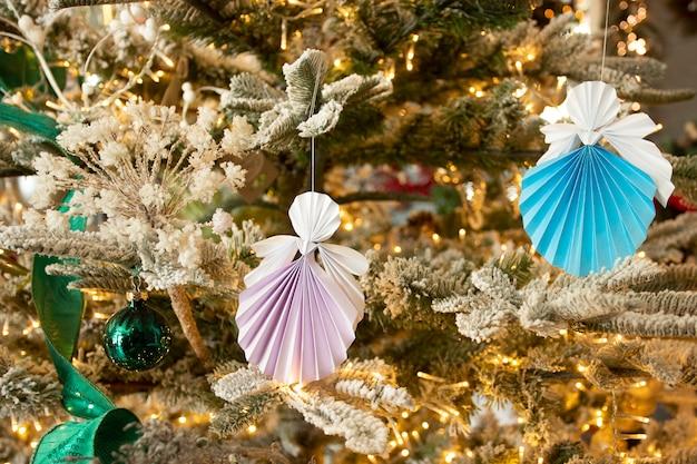 素敵な新年の手作りの天使のペーパークラフトの折り紙は、暖かいライトが付いている休日の室内装飾とクリスマスツリーに数字します。クリスマスコンセプト冬カードスタジオショットクローズアップ
