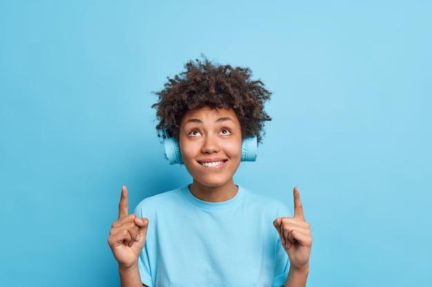 Хорошее предложение для вас. довольная любопытная женщина-модель с афро-волосами показывает указательными пальцами выше, показывает что-то над головой, слушает музыку из плейлиста через стереонаушники, изолированные на синей стене