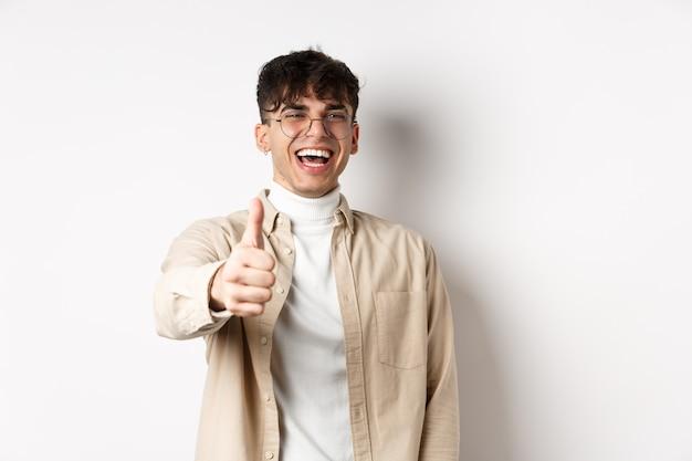 Хороший. счастливый молодой человек смеется и показывает палец вверх, как что-то хорошее, стоя на белой стене, комплимент вам.
