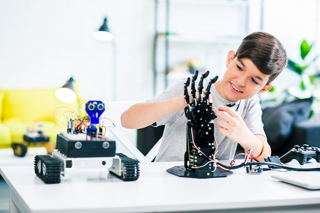 Симпатичный оптимистичный умный мальчик тестирует свое роботизированное устройство, пока он занимается инженерными классами