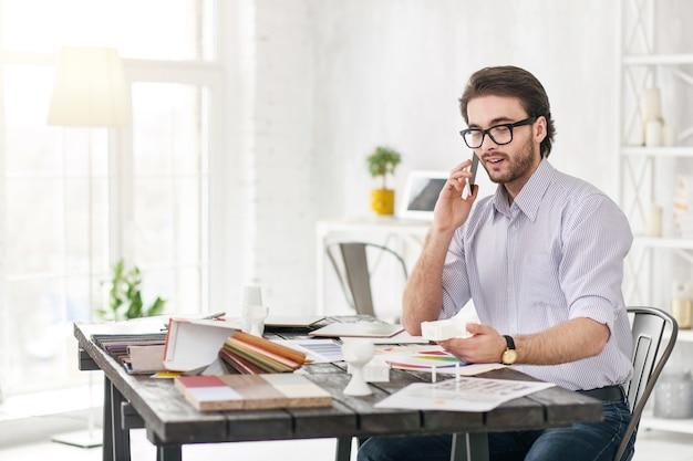 素敵な電話の話。電話で話し、白いオブジェクトを見てうれしそうなひげを生やしたマネージャー