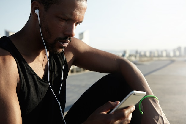 デジタルデバイスで実行するために音楽トラックを選択する若くてハンサムなアスリートの素敵な写真。孤独なアフリカ系アメリカ人の男性は、彼のトレーニングから休憩を取って、ヘッドフォンで美しい歌を楽しんでいます。