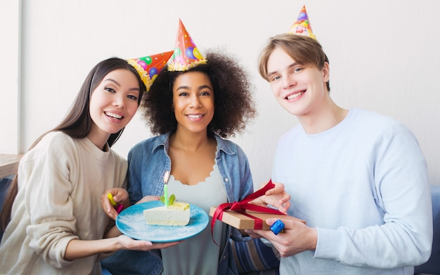 Nice picture of a birthday girl and her friends. asian girl has a piece of cake. the guy holds a present in his hands. all of them are happy.