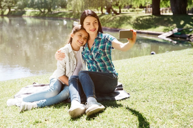 Nice picture of mom and daughter taking selfie. they are sitting on blanket near pond. woman is holding phone. they are looking at it and smiling. girls are posing.