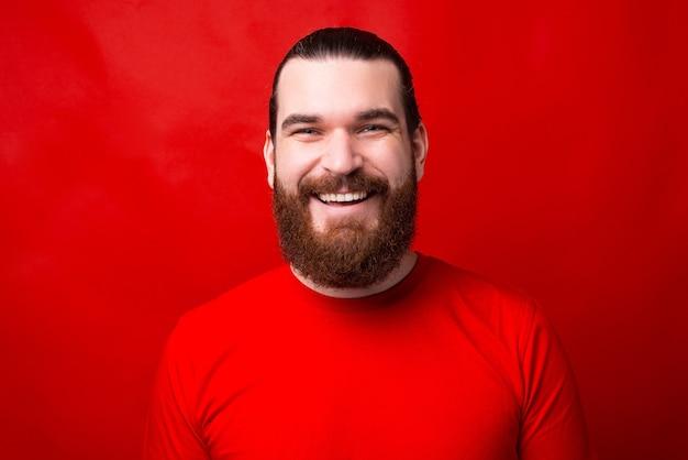 赤い壁の近くのカメラを見て笑っている男の素敵な写真