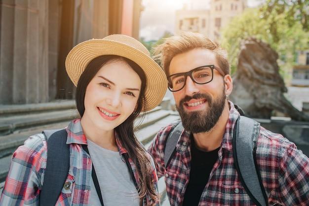 カメラで見ていると笑顔の2人の若い観光客の素敵な写真。男と女は階段の近くに外に立っています。彼らは背中にロックサックを持っています。人々は前向きで美しいです。