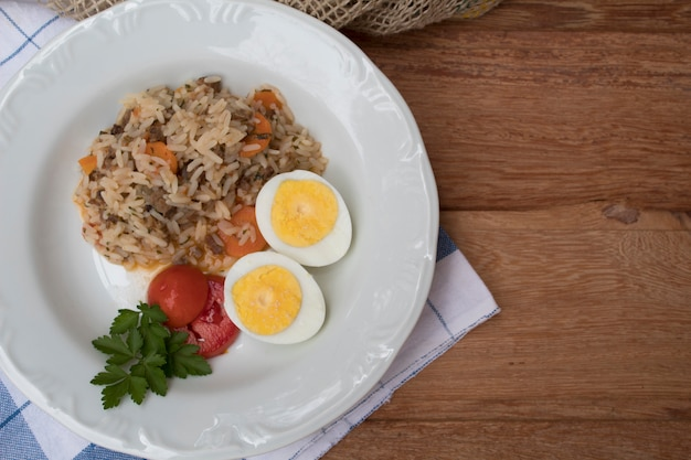 A nice plate of rice, boiled eggs and tomatoes in top view