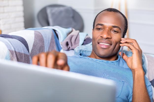 좋은 즐거운 성인 남자가 소파에 누워 전화로 말하는 동안 자신의 노트북을 사용