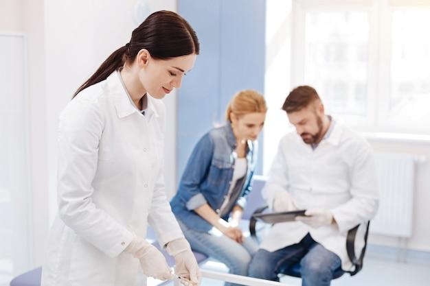 テーブルの近くに立って、彼の患者と対話するハンサムな専門の医者と注射器を準備している素敵な楽しい喜んでいる女性
