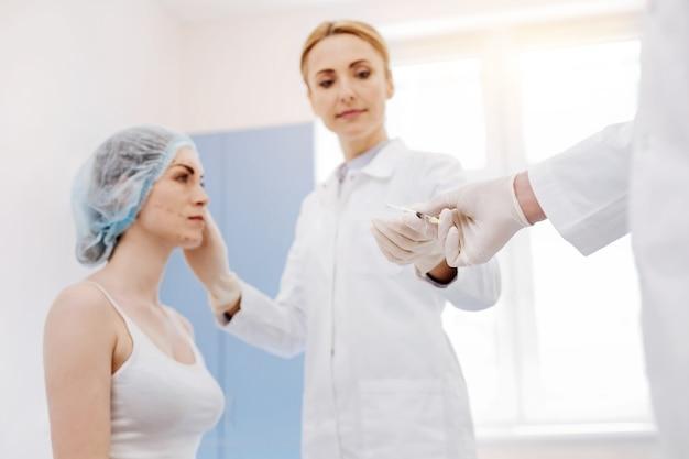일회용 장갑을 끼고 보톡스 주사를하는 동안 주사기를 복용하는 좋은 즐거운 여성 의사