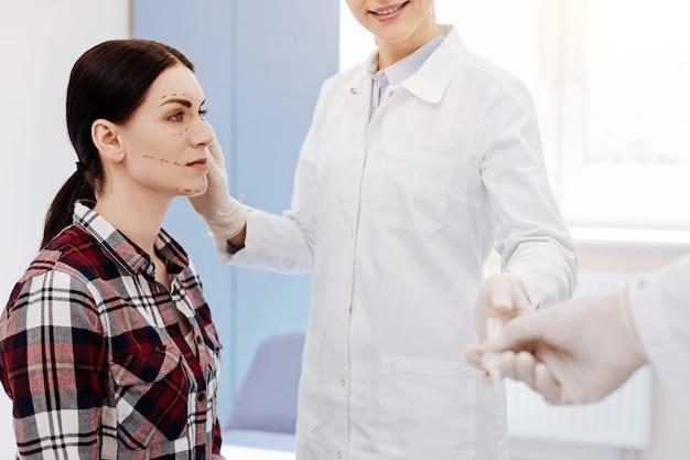아름답고 싶어하면서 의사 앞에 앉아 성형 수술을받는 좋은 즐거운 젊은 여성