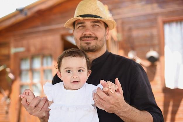 Симпатичный портрет маленькой девочки, которую держит ее отец на открытом воздухе