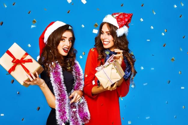 Хороший портрет двух счастливых молодых женщин в шляпе санта-клауса с подарком.