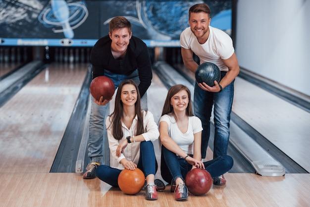 Bel ritratto. i giovani amici allegri si divertono al bowling durante i fine settimana