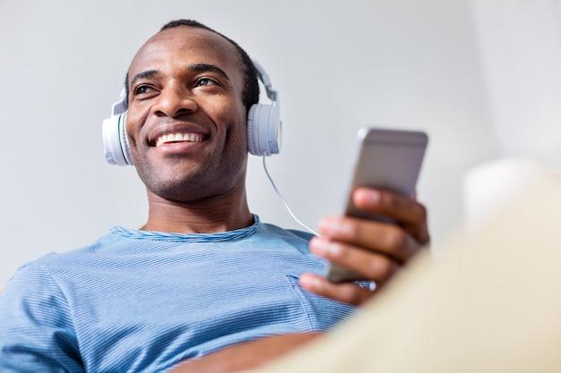 Хороший позитивный взрослый мужчина в наушниках и улыбается, слушая свою любимую песню