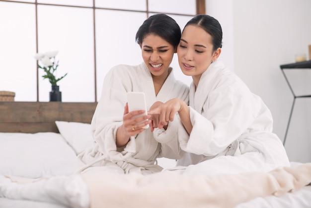 スマートフォンで写真を見ながらベッドに一緒に座っている素敵なポジティブな魅力的な女性