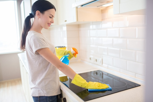 Nice and positive brunette stands in front of stove and cleans it with rag. also she holds blue liquid spray in left hand. girl wears yellow gloves.