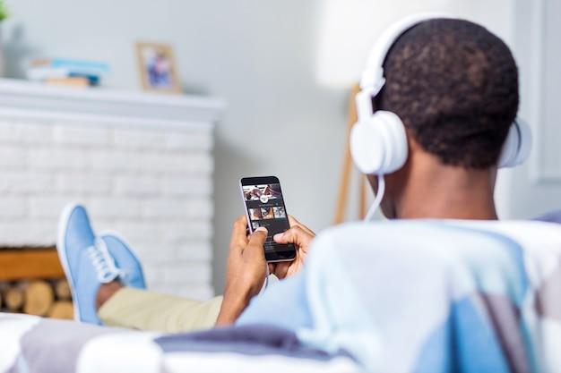 Хороший позитивный жизнерадостный мужчина использует свой смартфон и слушает музыку в наушниках, сидя на диване
