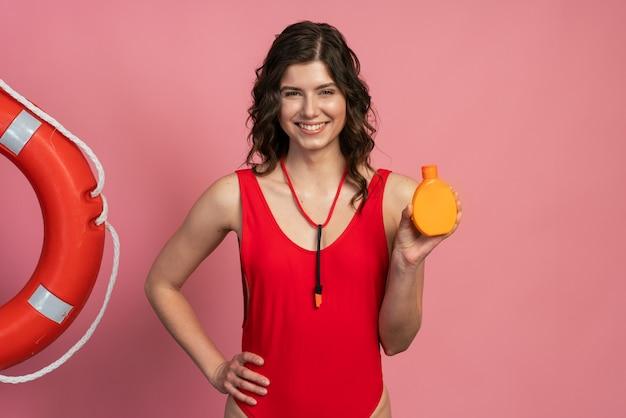オレンジ色のボトルを保持している赤い水着の素敵な、ポジティブな女の子。ピンクの背景にポーズをとる女の子