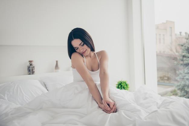 Милая позитивная девушка позирует в своей постели
