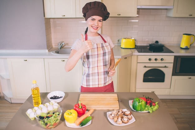 Nice and positive girl stands and poses. girl is ready to prepare food.