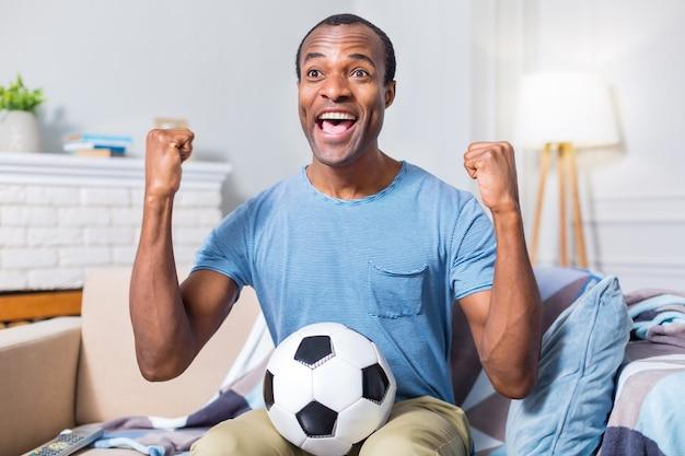 Хороший позитивный счастливый мужчина держит мяч и выражает свое счастье, будучи счастливым за свою футбольную команду