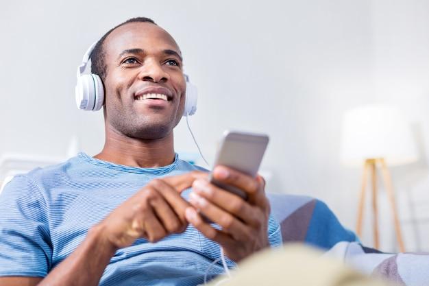 Хороший позитивный счастливый человек улыбается и держит свой смартфон, наслаждаясь музыкой