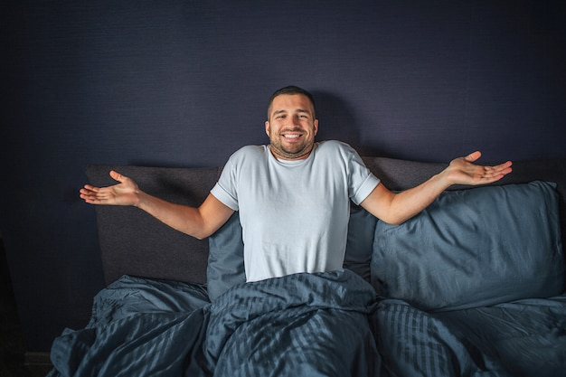 Nice and positive young man sitting on bed. he is covered with dark-blue blanket. he keeps hands aside of body. guy smiles. he is happy.