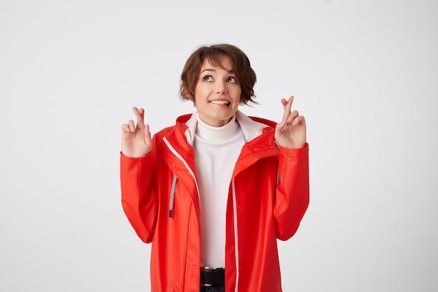 흰색 골프와 빨간 비옷을 입은 멋진 긍정적 인 젊은 짧은 머리 아가씨, 입술을 물고 복사 공간을 바라보고 손가락을 교차하고 행운을 기대합니다. 서 있는.