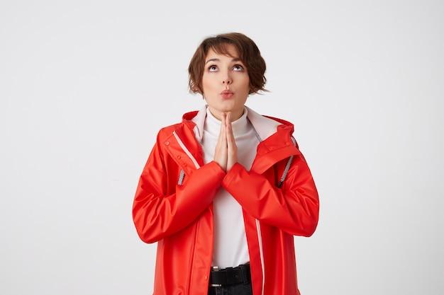 하얀 골프와 빨간 비옷을 입은 좋은 긍정적 인 젊은 짧은 머리 아가씨, 복사 공간을 올려다보고,기도 제스처를하고 행운을 기원합니다. 서 있는.