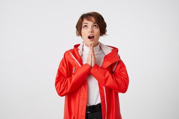 白いゴルフと赤いレインコートを着た素敵なポジティブな若い短い髪の女性は、コピースペースで大きく開いた口で見上げ、祈りのジェスチャーをし、幸運を願っています。立っている。