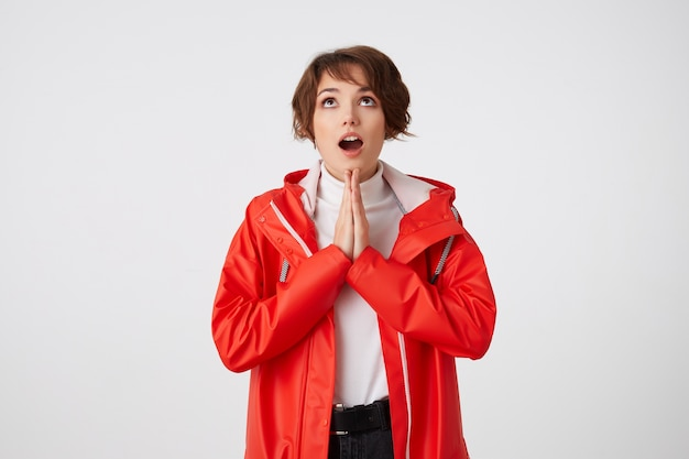 Bella giovane signora dai capelli corti positiva in golf bianco e impermeabile rosso, guarda in alto con la bocca spalancata nello spazio della copia, fa un gesto di preghiera e spera di fortuna. in piedi.