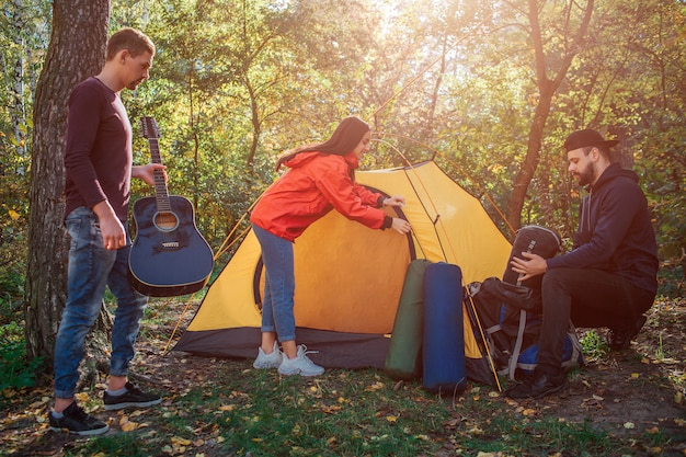 Nice and positive young woman closing enter of tent. guy on left has guitar in hands. young man on right sits and gets sleeping bag out of rocksack.