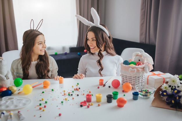 Nice positive young woman and her daughter prepare for easter. they stand behind table in room and look at each other. mother and daughter smile. they wear bunny ears.