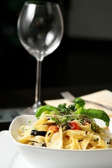 Хорошо приготовленные тальятелле на столе с вилкой и вином